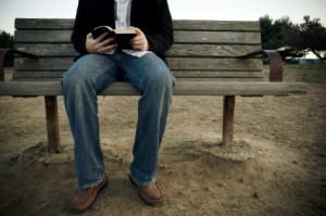 Man on a bench reading his Bible